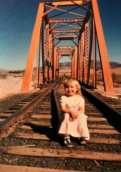 Little girl sitting on rail tracks